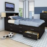 bold wooden brown storage bed nyc design with blue bed sheet and white pillow and plaid patterned area rug and wall palette and wall lamp