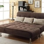 Brown Tufted Queen Sleeper Sofa With Some Pillow And Standing Lamp Plus Wooden Bookcase And Wooden Floor