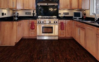 classic kitchen idea with beige colored wooden cabinetry on dark wooden vinyl plank floor idea with modern lighting