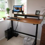 comfortable modern office corner with homemade standing desk with adjustable mode with black frame and file cabinet and potted plant  with glass windows