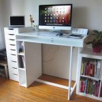 compact standing desk design in white color with bookshelves and flat file cabinet and potted plant on hardwood floor