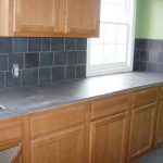 concrete backsplash that is designed in black tiles for kitchen storage systems form kitchen