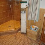 cork floor in bathroom with modern walk in shower with glass wall and tile for shower plus towel holder