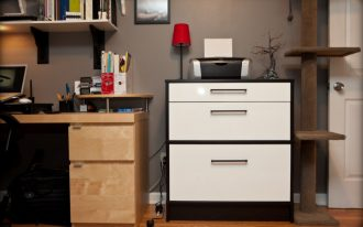 elegant and modern white flat file cabinet from ikea with red table lamp in office with wooden desk and wall rack