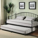 elegant metal scrolled day bed with trundle pop up and stripe patterned bolster and pillows with wall gallery photo