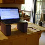 elegant natural wooden standing desk office with additional tiny table in large office with glass door and window