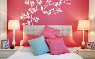 elegant soft pink bedroom with white bedding with pink pillow and blue accent and double nightstands with table lamps and washable paint for wall