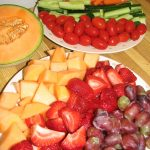 fresh and fun snack ideas for parties  with fruit salads of grapes, strawberries and melon plus cucumber and carrot