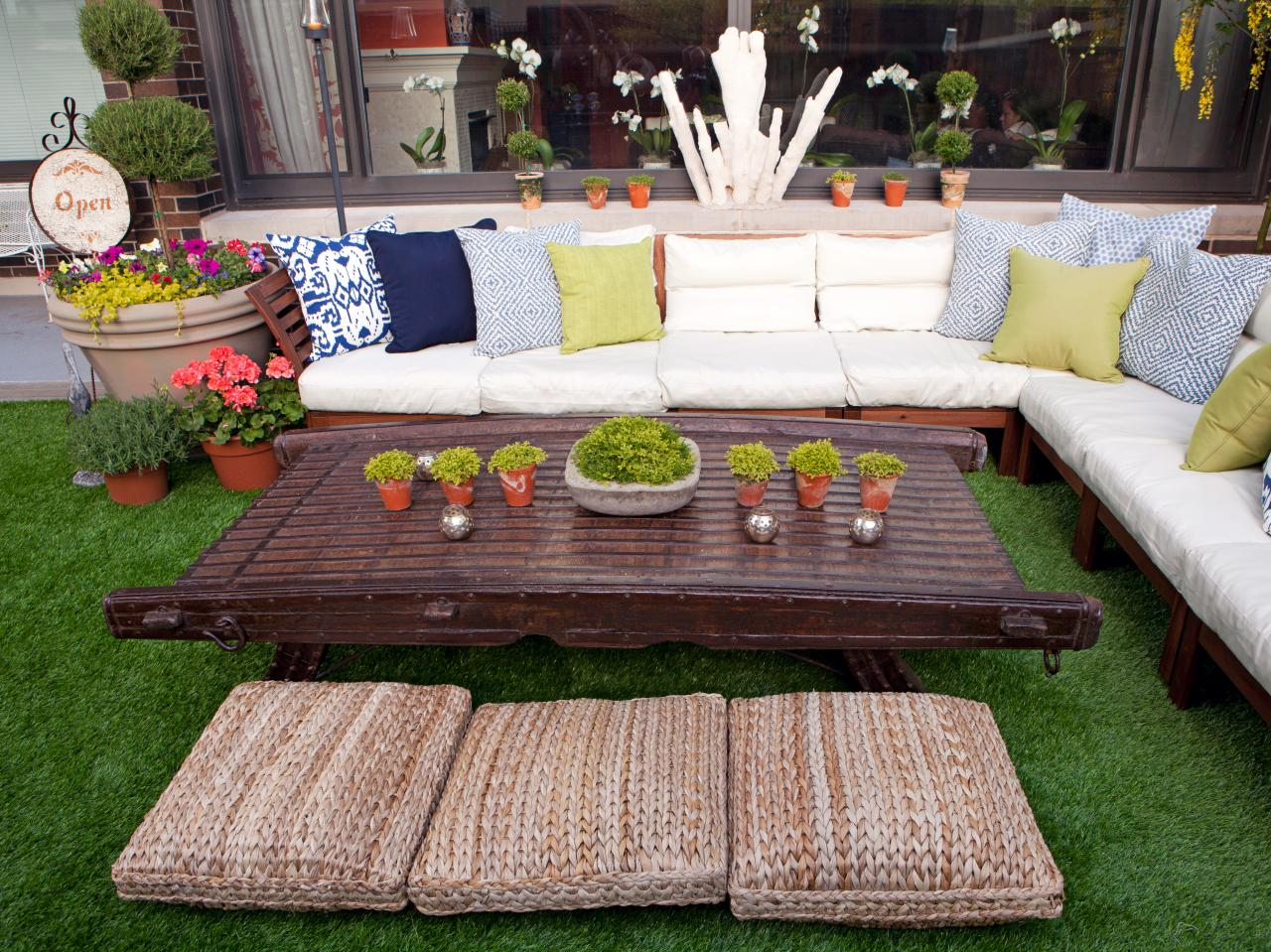 fresh and stunning brown wooden kid friendly coffee table design with potted plants with rattan pouf before sectioned white sofa