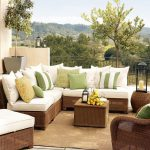 fresh white green pottery barn couch design with rattan frame and rattan coffee table with lush vegetation and mountain view on cream area rug