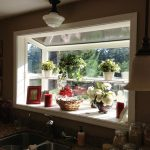 greenhouse windows for kitchen above kitchen sink beautified with green plants and flower plus candle and picture fram plus traditional pendant light fixture