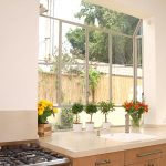greenhouse windows for modern kitchen above kitchen sinkadorned with green pllant and colorful flower pot and modern kitchen cabinets and appliaces