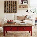 industrial red kid friendly coffee table made of wood with storage with creamy top before white sofa beneath floor lamp with wall decoration