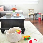livable interior design with gray modern sofa and black oak kid friendly coffee table with storage on patterned white area rug with kids toys