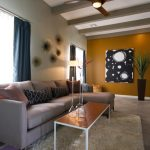 mid century modern ceiling fan decorated in living room with comfy beige sofa and decorative cushions and soft rug with coffee table and wall ornament