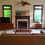 mid century modern ceiling fan for living room with brown sofa and wooden coffee table plus area rug and fireplace plus wooden tv stand plus nightstand