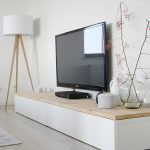 minimalist white long media cabinet design with cream top and television set with dried plant and tripod floor lamp
