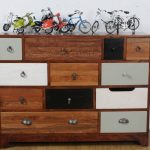 mix of color chest of drawer design with various size of drawer with botton handle with bicyle decoration on its top