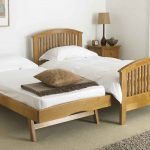 natural day beds with pop up trundle with wooden platform bed with corner nightstand and table lamp with brown pillow and sheet