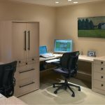 office design for two persons with white tone modular desk components with cupboard beneath cream wall with picture