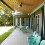 outdoor mid century modern ceiling fan on wooden ceilinf with turqouise chairs and retro furniture for porch