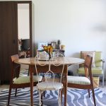 rug on top of carpet  with zebra pattern in dining room with traditional round wooden table plus wooden chairs and metal vintage chairs plus bookcase and armchair