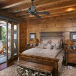 Rustic Bedroom Decor Idea Consisting Of Wood Bedside Tables With Table Lamps In Rustic Style Natural Toned Bedroom Rug Settee Furniture Made Of Hardwood  Black Ceiling Fan Hardwood Planks Wall System