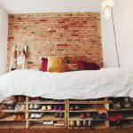 shabby look bedroom design with brick wall accent and white bedding with storage nyc for shoes and stair rack