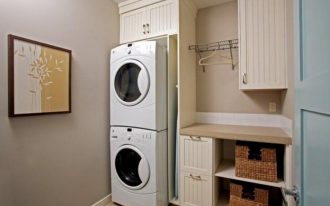 simple laundry room design with dull white cabinetry and recessed smalles stackable washer dryer design with storage bins