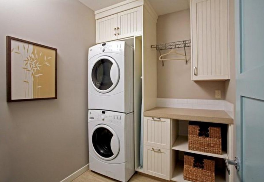Simple Laundry Room Design With Dull White Cabinetry And Recessed Smalles Stackable Washer Dryer
