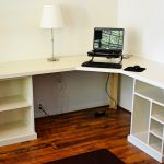 simple modular desk component design in white color with storage and table lamp on hardwood floor beneath white wall