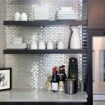 small size subway tiles backsplash in stainless steel floating shelves for organizing the dishware collections white porcelain kitchen counter a picture frame