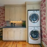 small stackable washer dryer combo design in beautiful tropical kaundry room design with floral patterned wall and white cabinetry with wooden floor and large glass window