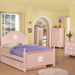 spacious children bedroom design with soft pink furniture idea and kids twin beds with storage on brown floor and yellow wall paint