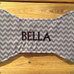 stunning personalized dog mat design in bone shape with chevron pattern with bella spelling on the surface