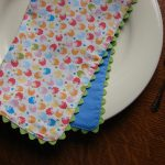 sweet colorful  balloon patterned cloth napkin design with chevron edging with blue background on white plate with spoon