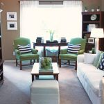 tidy family room with pottery barn couch design and polka dot patterned cushion and wooden coffee table and large storage and green arm chairs