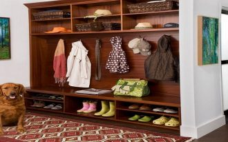 traditional wooden mudroom storage units with shoes storage underneath plus hats and modern entry rug and wooden laminate floor