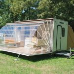 unique designed mobile home that looks like house with fan style of transparent roof on grassy meadow beneath lush vegetation