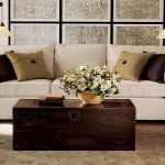 vintage wooden coffee table design with white flower decoration and white pottery barn couch with silky cushions beneath froted glass wall accent