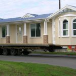 walking mobile home that looks like house in ywllow tone with glass window and gray roof on road aside grassy meadow