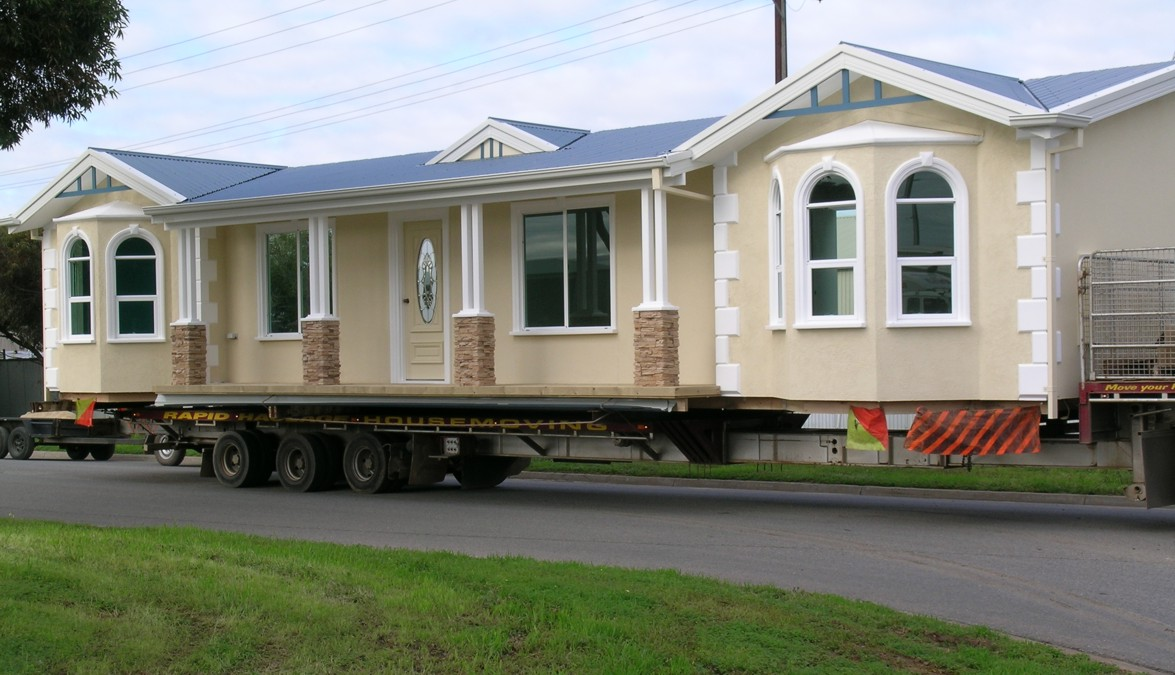 walking mobile home that looks like house in ywllow tone with glass window  and gray roof