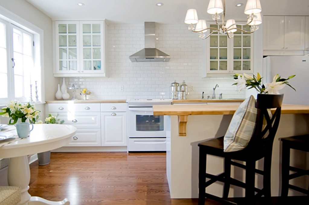 White Kitchen Backsplash Ideas HomesFeed : white ceramic tiles kitchen backsplash idea white kitchen cabinets glass door top cabinets with trims classic pendant chandelier fixture a kitchen island with wood top and black painted wood chairs from homesfeed.com size 1023 x 679 jpeg 172kB