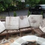 wonderful wooden pottery barn couch design with white bolsters before round fire pit on stone flooring beneath shady trees