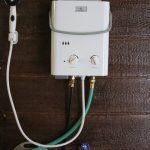 white water heater with brown wooden wall