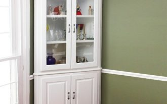 A corner hutch storage idea with white stain and glass door
