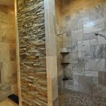 A doorless shower idea with natural stone walls corner shelves a heldhand showerhead fixture wall mount showerhead fixture mosaic tiles floors idea