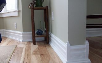 Beautiful decorative home baseboard in white lighter grey wall system unfinished wood planks floor idea an entryway mat a console table as corner decoration