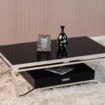 Black glass top table in rectangular shape which has stainless steel legs and black storage box underneath thick white shag rug idea