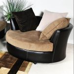 Black leather round chair with headrest feauture brown cushion brown white and black throw pillows